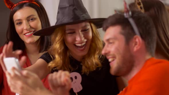 Friends in Halloween Costumes with Smartphone
