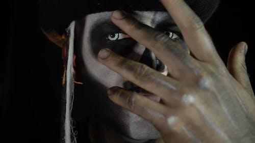 Man in Skeleton Halloween Cosplay Costume. Guy in Creepy Skull Makeup Looking at Camera