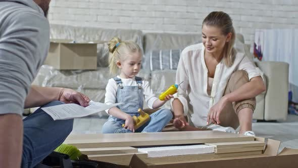 Thumbnail for Girl with Toy Screwdriver Helping Parents