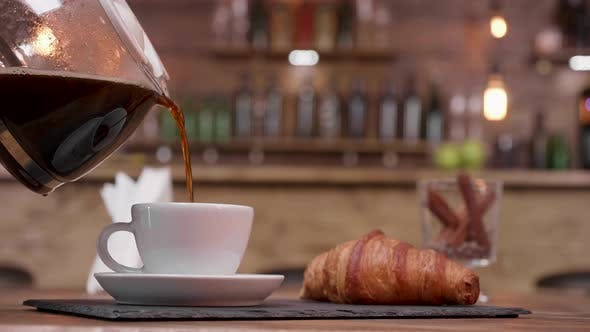 Thumbnail for Close Up Shot of a Coffee Pot Filling a Cup To Serve with Croissant