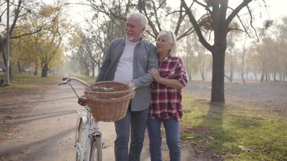 Thumbnail for Happy Senior Caucasian Couple Walking with Bicycle Along the Alley in the Foggy Park