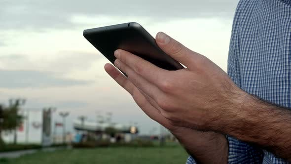 Thumbnail for Man Clicks on a Digital Tablet at Sunset