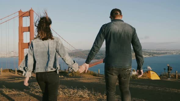 Thumbnail for Back View Happy Man and Woman Walk Together Holding Hands at Epic Beautiful View of Golden Gate