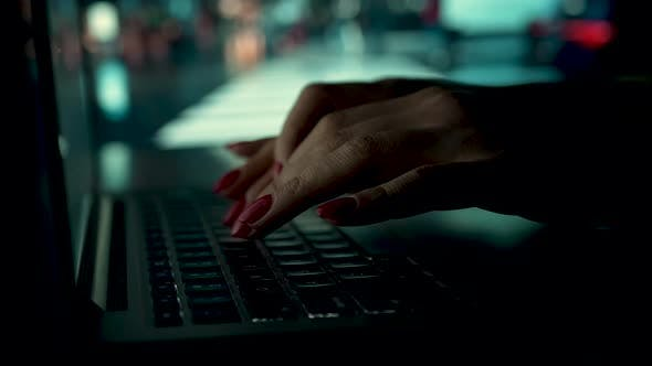 A Woman Works on a Laptop at Home on a Blurred Background of a Working TV