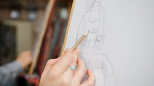 Close-up of Female Hand Drawing Portrait of Woman with Pencil on Paper in Arts Class