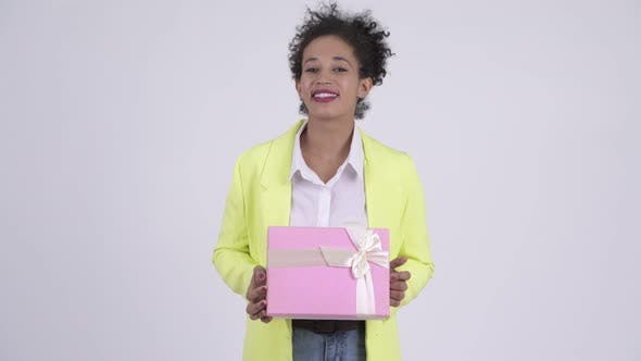 Cover Image for Happy Young Beautiful African Businesswoman Thinking While Holding Gift Box