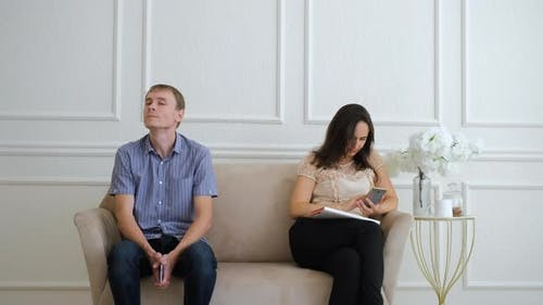 Man and Woman Sitting on Sofa in Waiting Area