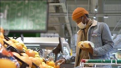 Professional Shopper in Face Mask Chooses Yellow Lemons