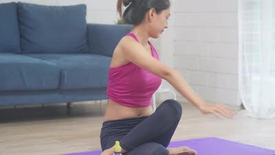 Young Asian woman practicing yoga in living room.