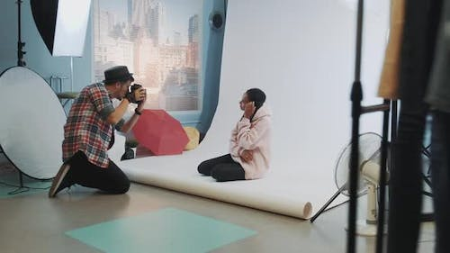 Backstage of the Photo Shoot: Black Model Posing on the Floor for a Photographer