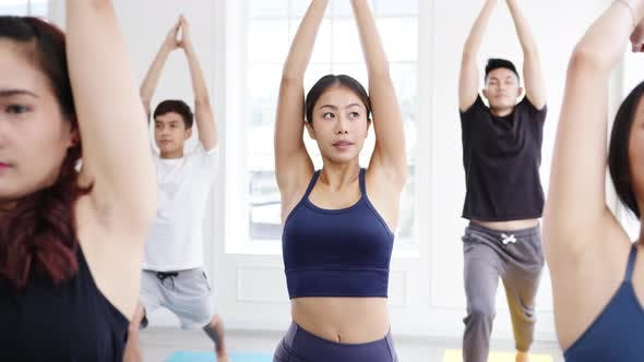 Asia group of women exercising yoga healthy lifestyle in fitness studio.