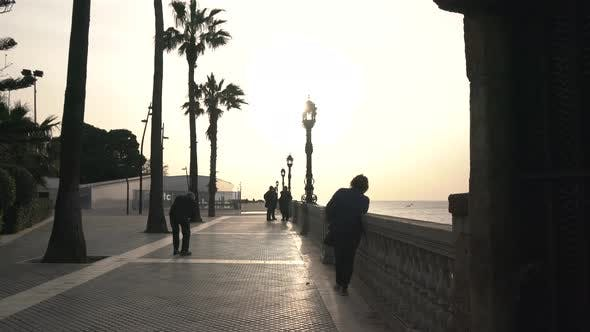 People on a promenade at sunset