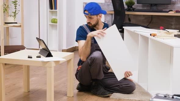 Thumbnail for Männlicher Arbeiter im Overall montiert neue weiße Möbel