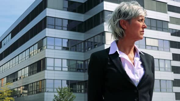 Thumbnail for Business Middle Age Woman Looks Around - Company Building in the Background