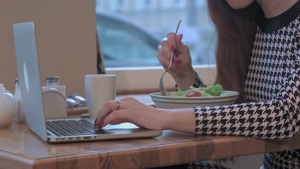 Thumbnail for Arms of Young Businesswoman Using a Laptop for Work. She Is Sitting at the Table in Cafe and Eating