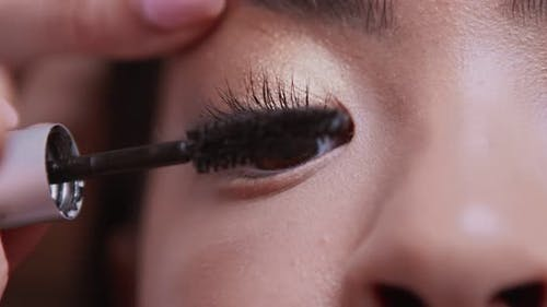 Close Up of Make Up Artist Painting Client Lashees with Professional Mascara