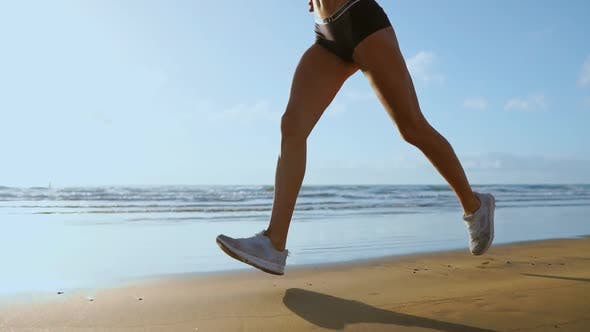 Leg Sporty Woman in White Sneakers Running Along Beautiful Sandy Beach