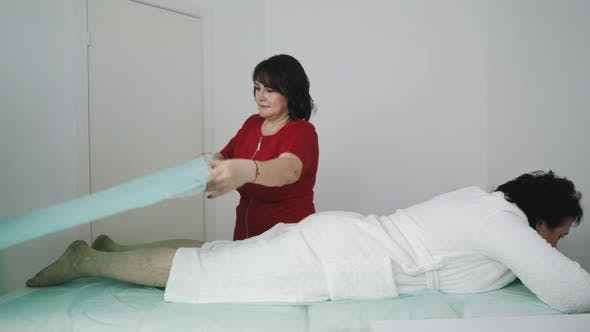 Therapist Covers Legs of Middle Aged Patient with Fabric