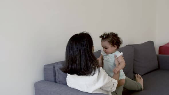 Back View of Mom Lying on Sofa Lifting Cute Daughter Over Head