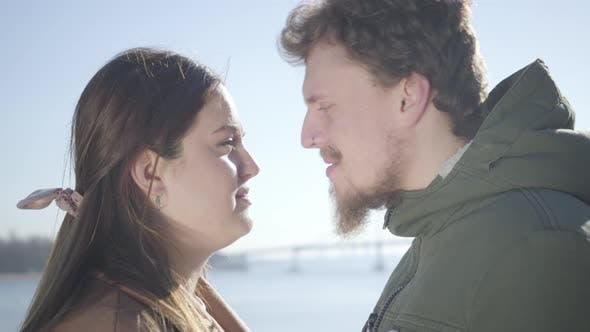 Thumbnail for Close-up of Smiling Caucasian Man with Nose Ring and Chubby Brunette Woman Rubbing Noses on River