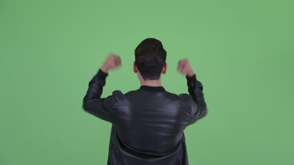 Thumbnail for Rear View of Happy Young Multi Ethnic Man with Fists Raised
