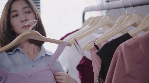 woman shopping clothes. Shopper looking at clothing on the rail indoors