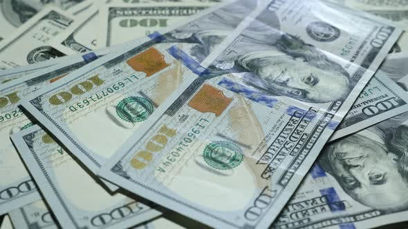 Hundred dollar banknotes are spinning on table