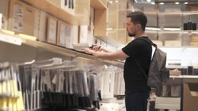 Male Shopper is Examining Kitchen Knifes in a Store in Mall