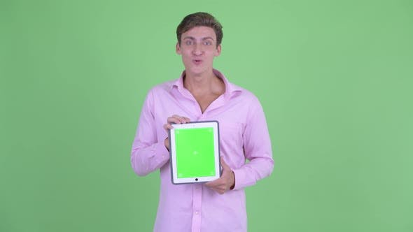 Thumbnail for Happy Young Handsome Businessman Showing Digital Tablet and Looking Surprised