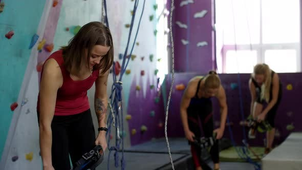 Thumbnail for Three Women Putting on Safety Gear next to Indoor Climbing Wall