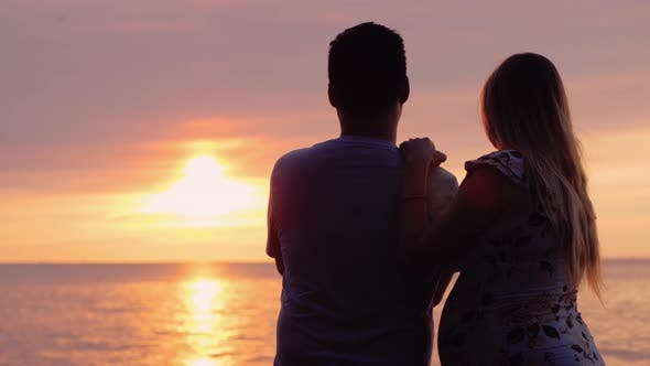 Thumbnail for Asian Man with Pregnant Wife Enjoy Sunset Over the Ocean