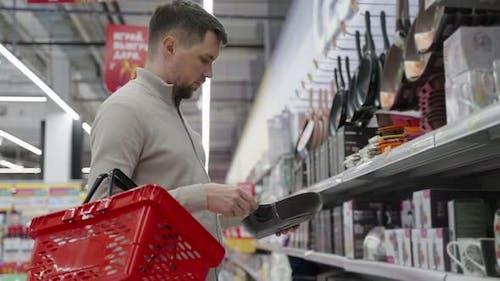Single Man is Shopping in Hypermarket Choosing Frying Pan in Tableware Department