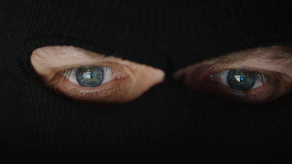 Thumbnail for Eyes of thief in a black mask (balaclava) before a computer