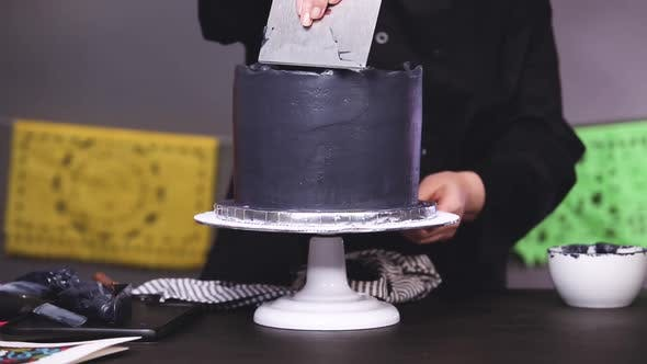 Thumbnail for Step by step. Baker frosting multilayer chocolate cake with a black italian buttercream frosting.