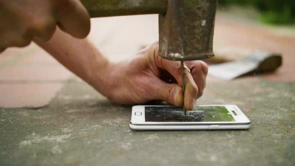 Thumbnail for A Man Hammers a Nail Into the Phone on the Concrete Ground in Slow Motion