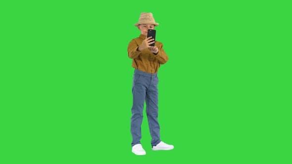 Kleiner Junge mit Strohhut, der Selfies auf seinem Handy auf einem Greenscreen Chroma Key macht