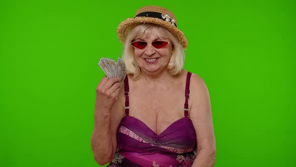 Mature Grandmother Traveler Rejoicing Winning Lottery Waving Bunch of Money Dollars Cash Smiling