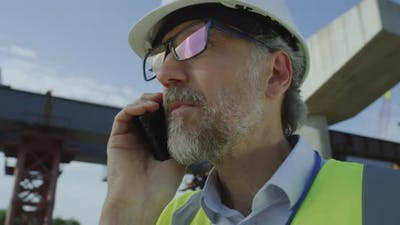 Mature Contractor Speaking on Smartphone
