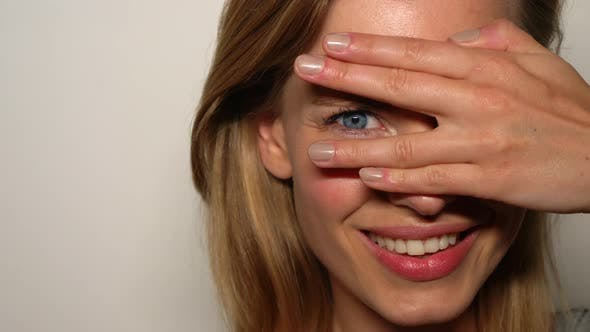 Model with Her Eyes Covered with One Hand and Peeks Through Her Fingers