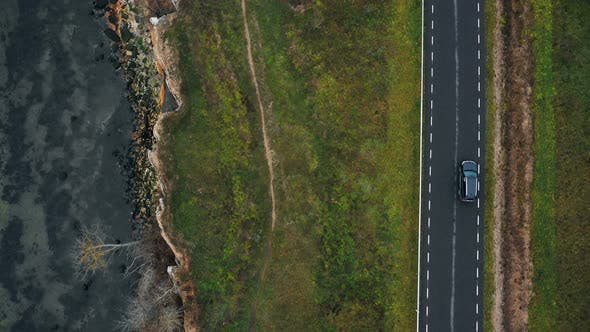 Thumbnail for Top View Drone Tracking Black Car Moving Along Autumn Bay Road Very Close To Beautiful Eroded