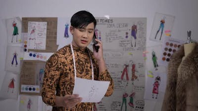 Fashion designer man talking on mobile phone with customer