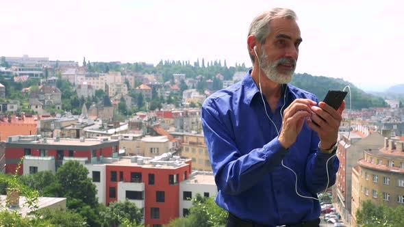 Thumbnail for Old Senior Man Listens Music with Earphone on Smartphone - City (Buildings) in Background