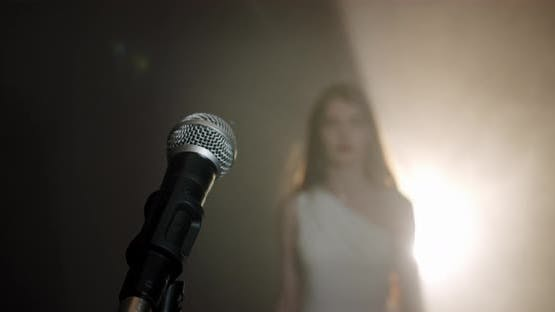 The Girl Singer Approaches the Microphone and Begins To Sing, the Scene in Smoke. Close Up