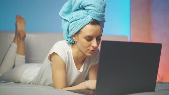 A Attractive Smiling Woman Is Typing Text Message and Using Laptop While at Home