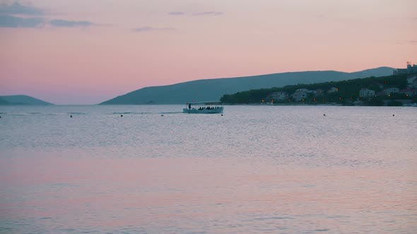 Thumbnail for Transporting Boat with People Swimming on Sea at Sunset