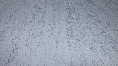 Water Drops Following Down on Gray Background