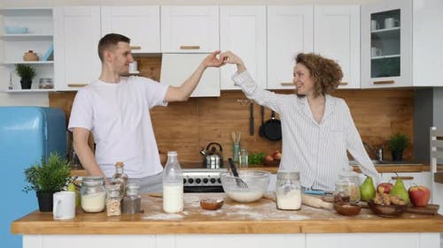 Happy Family Couple Dancing In Kitchen Celebrating Good Morning Full Of Positive Emotions