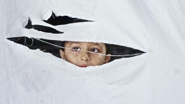 Thumbnail for Little Refugee Boy Hiding behind Cloth