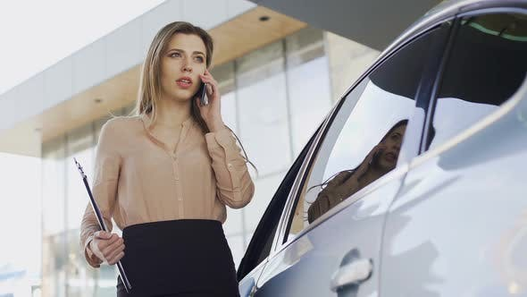 Cover Image for Confident Businesswoman Talking on Smartphone With Client Near Parked Car