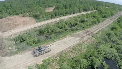 Flying over tank driving on rough ground in the woods